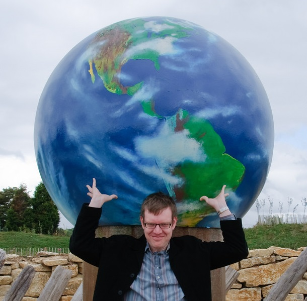 some guy with glasses posing under a globe like he's carrying the weight of the world